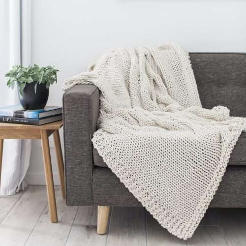 Beautiful white knitted blanket draped over a sofa