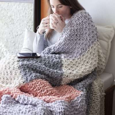 Woman wrapped in a knit blanket drinking from a coffee cup.