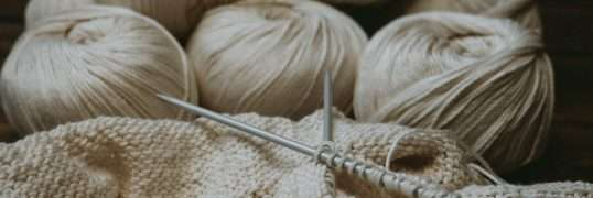 Knitting project with knitting needles and white yarn
