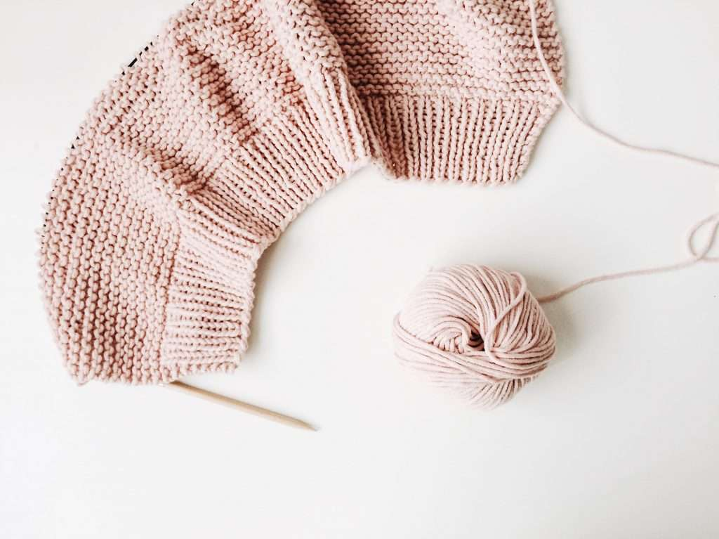 Circular needles with a project made of pink yarn