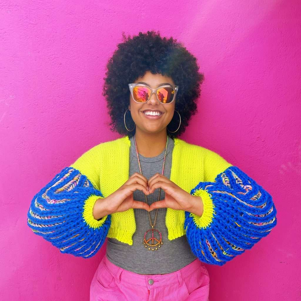 ElectroCardi by Disco Stitch in yellow and blue. Model has her hands in the shape of a heart.