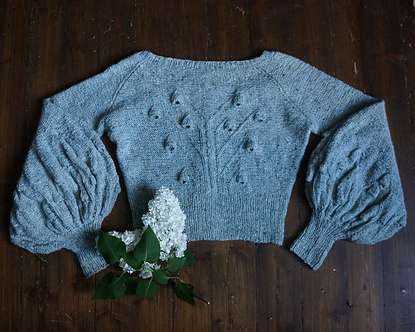 Fabel Knitwear Sylphide Jacket in blue. Jacket is on a table with back displayed, showing the bluebell pattern on the back and sleeves.